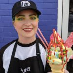 DANG Ice Cream worker shows off colorful cone.