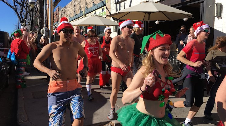 Image of 2018 Santa Speedo Dash includes men and women in bathing suits and other costumes.